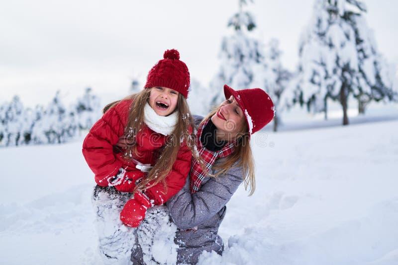 Modern går med hennes dotter i snöig vinter parkerar arkivbild
