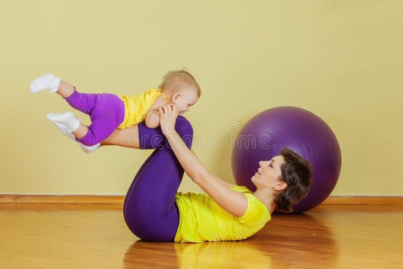 Modern gör övningar med hennes dotter arkivfoto