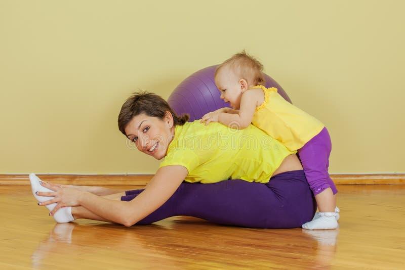 Modern gör fysiska övningar med hennes dotter arkivfoton