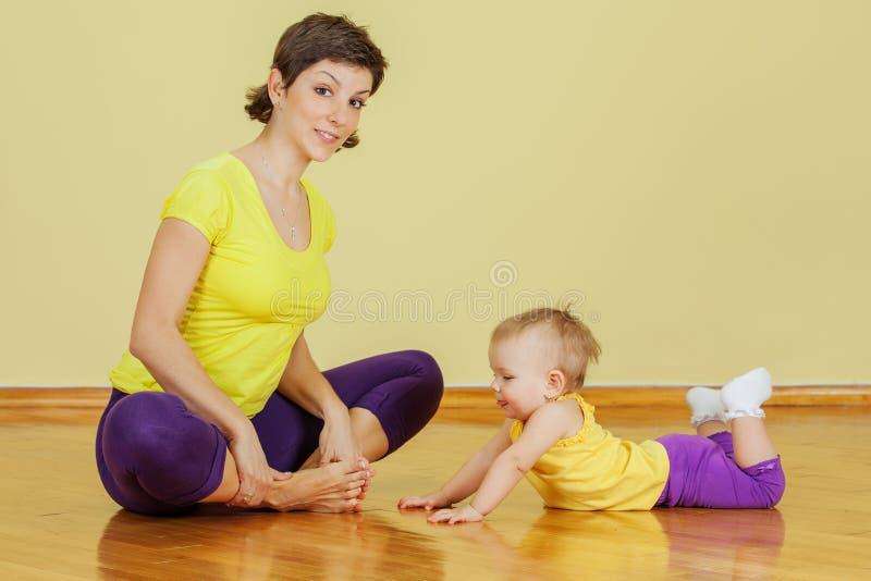 Modern gör fysiska övningar med hennes dotter royaltyfria bilder