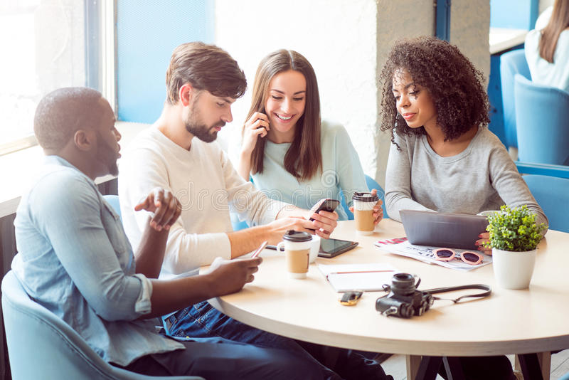 Modern gadgets in our life. What fun. Cheerful and smiling group of modern young people sitting in a cafe and drinking coffee while using their cell phones royalty free stock photography