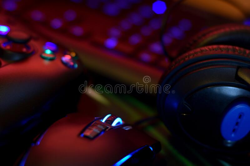 Modern gamepad and gaming mouse lies with keyboard and headphones on table in dark playroom scene. Devices for playing video games. Modern gamepad and gaming royalty free stock photos