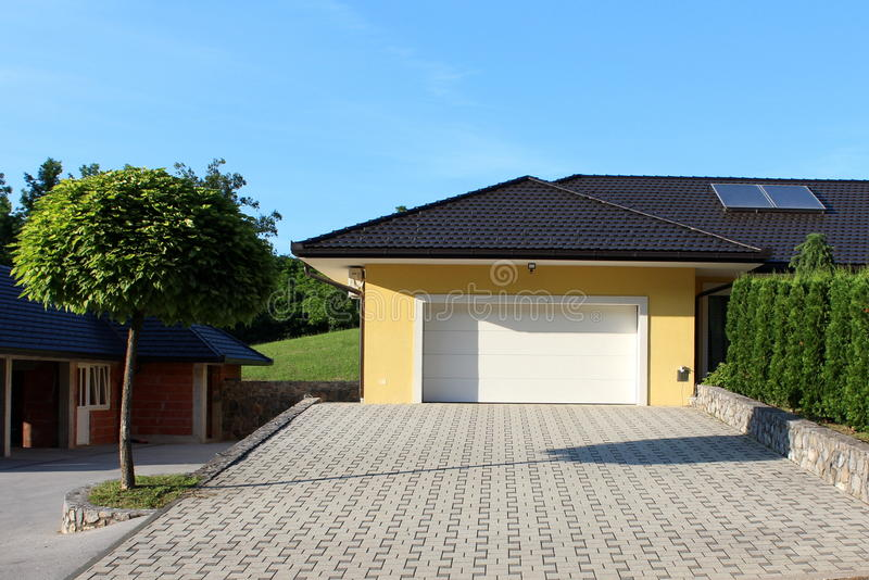Modern garage doors with stone tiles entrance royalty free stock photo