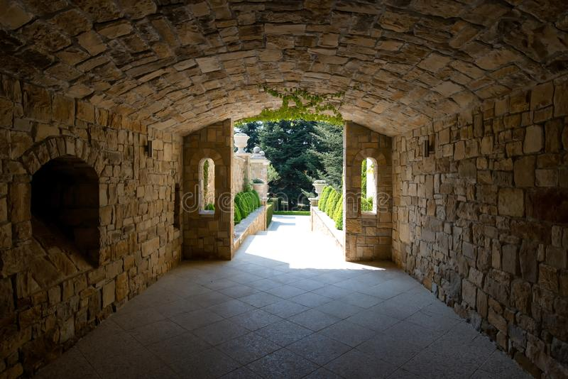 Modern garden design with a stone tunnel leading to a garden path decorated with conical green bushes stock image