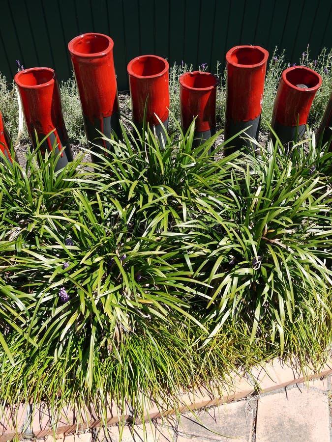 Modern garden: red ceramic sculptures grass border royalty free stock photography