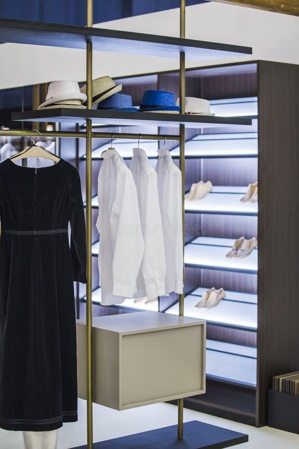 Modern garderob i lägenheten med kläder och hyllor för skor Skjortor och klänningar, hattar och skor i en trendig dressing fotografering för bildbyråer