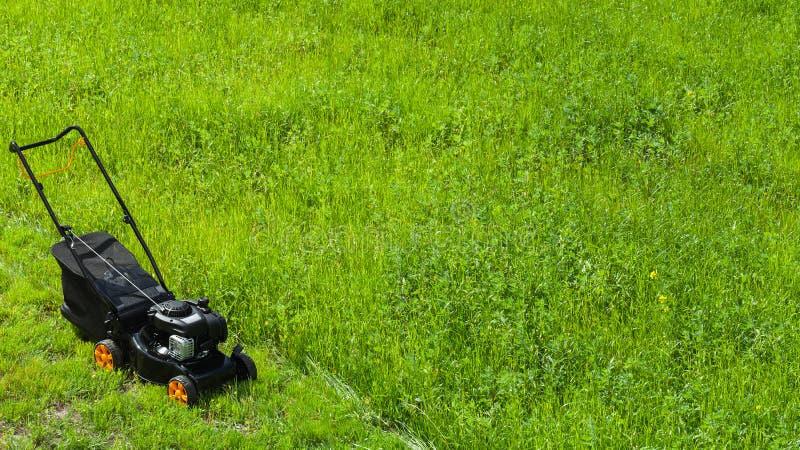 Grass cutter stands on fresh green lawn. Modern gasoline powered rotary push mower or grass cutter stands on fresh green lawn stock photo