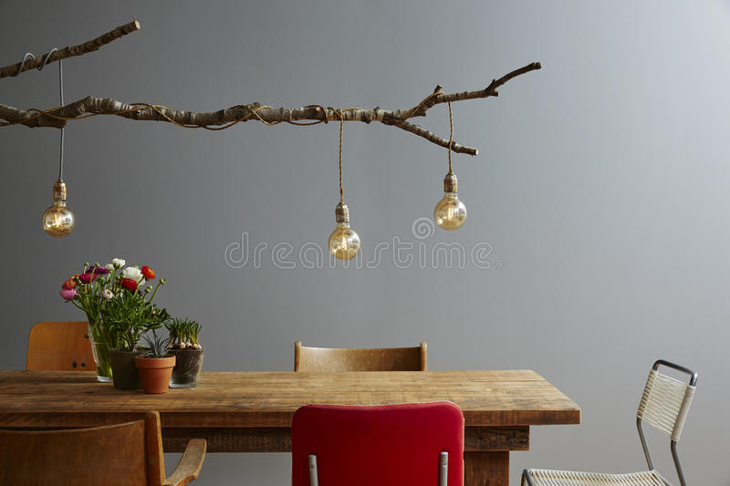 Modern gastronomy urban style wooden table with branch lamp. Creativity with birch and bulbs unique design stock image