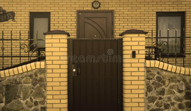 Modern geel de baksteenplattelandshuisje van metaalpoorten stock afbeelding
