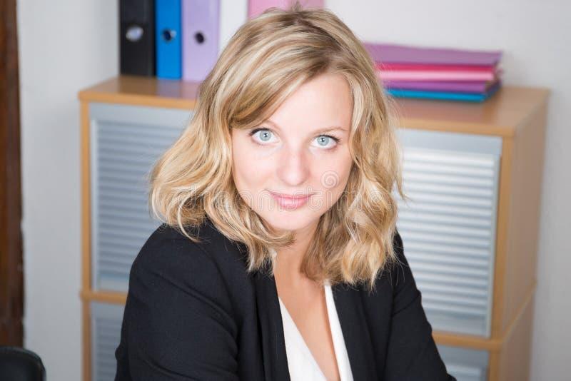 Modern gelukkig toevallig onderneemsterblonde die met blauwe ogen bij haar werkplaats in bureau zitten stock afbeelding