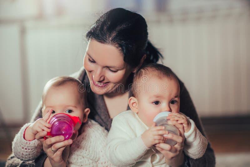Modern ger tvilling- behandla som ett barn flaskor fotografering för bildbyråer