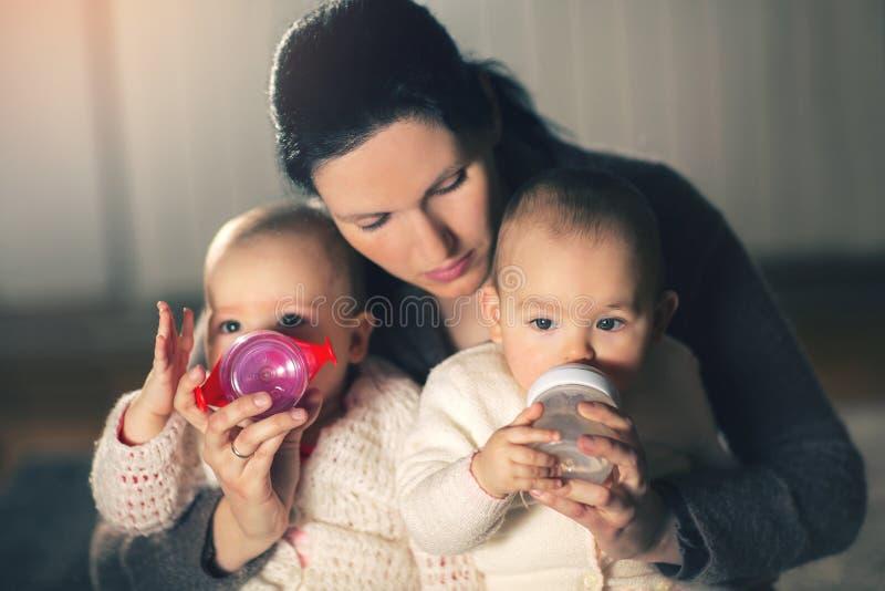 Modern ger tvilling- behandla som ett barn flaskor royaltyfri bild
