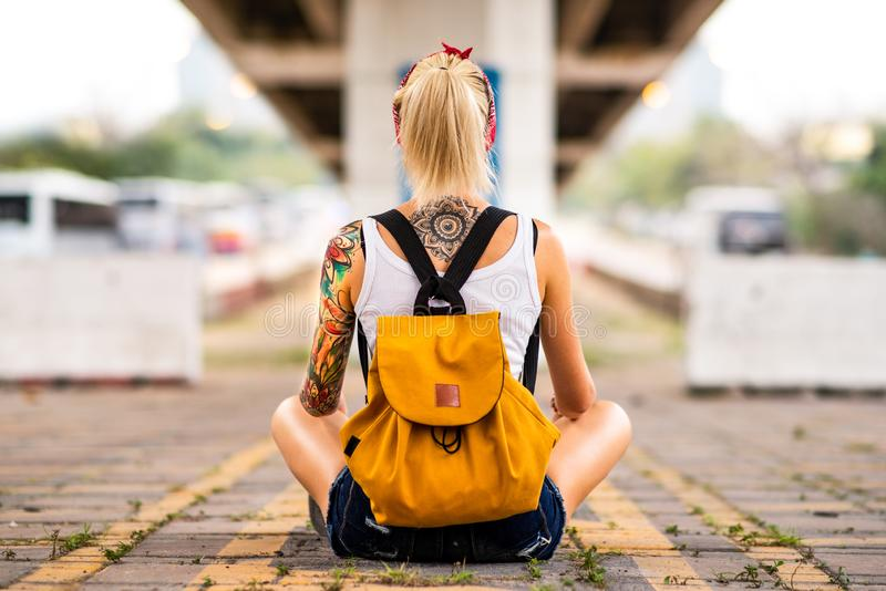 Modern girl sits with his back to the camera on a road marking. Carries a yellow backpack, arms tattooed.  royalty free stock images