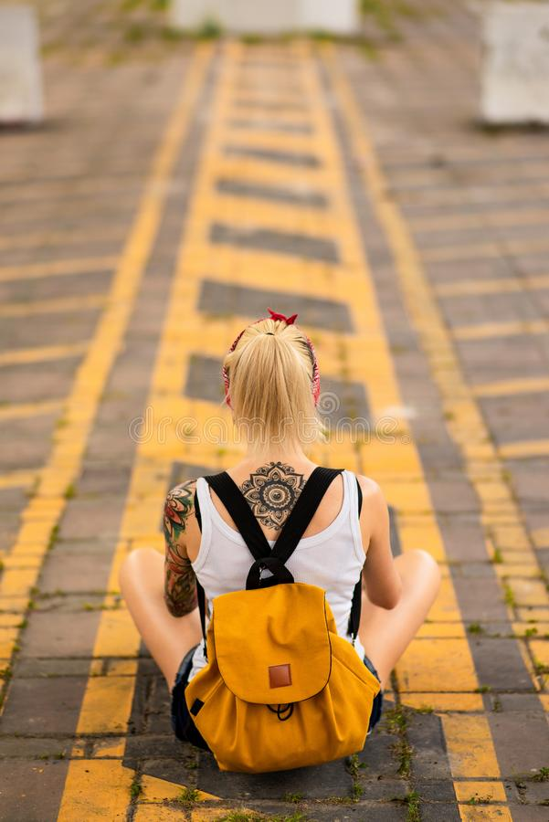 Modern girl sits with his back to the camera on a road marking. Carries a yellow backpack, arms tattooed.  royalty free stock photography