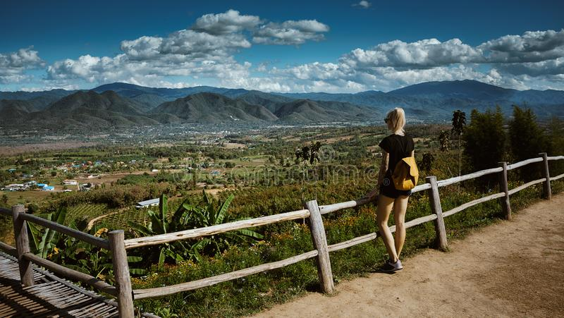 Modern girl with tattoos looks from above a beautiful view of the city of Pai. She is wearing a backpack and denim royalty free stock photography