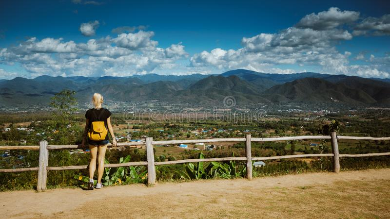 Modern girl with tattoos looks from above a beautiful view of the city of Pai. She is wearing a backpack and denim stock photo