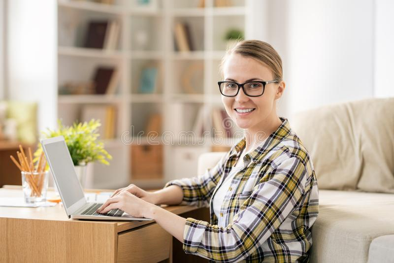 Modern girl using laptop at home stock image