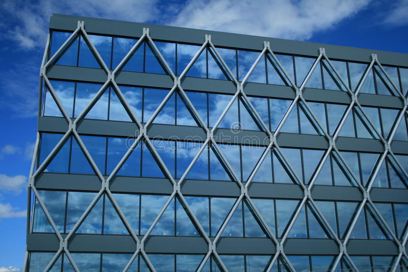 Modern glass building. Architrectural details of exterior of modern glass building with clouds reflected on windows royalty free stock photo