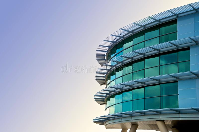 Modern glass building. Exterior of modern glass building with curving glass facade and blue sky background with copy space stock images