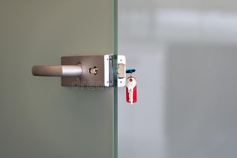 Modern glass door with metal alloy handles and key chain in lock, home or office security concept stock images