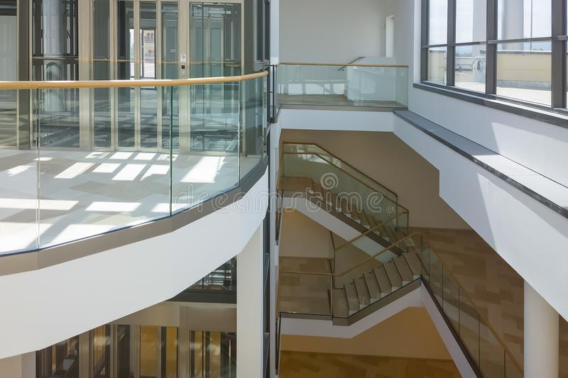 A modern glass elevator with stairs in a public building.  stock images
