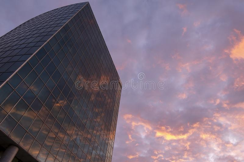 Modern glass high rise business building with reflected sunset in it. Wallpaper. Evening red clouds. Copy space. Great city view royalty free stock photography