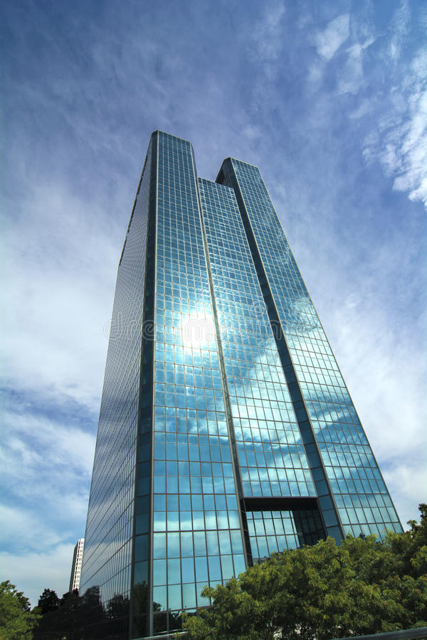 Modern Glass Skyscraper. A view of a glass window skyscraper in downtown Toledo Ohio. A beautiful blue sky with white clouds reflecting in the glass windows royalty free stock images