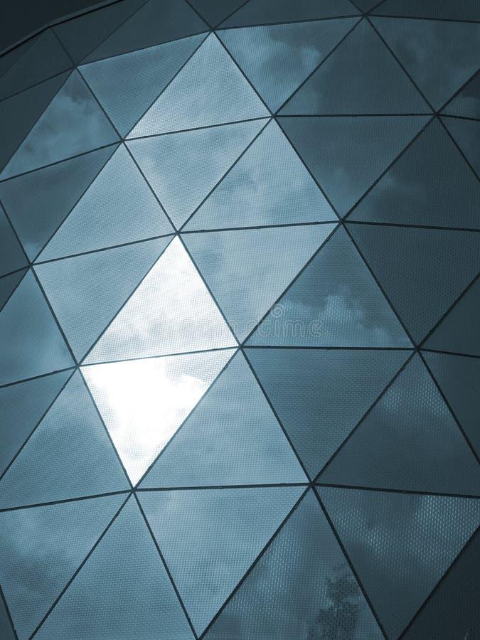 Modern glass triangular cladding windows with sky and clouds ref. Modern glass triangular shiny clad mirror windows with sky and clouds reflected stock photos