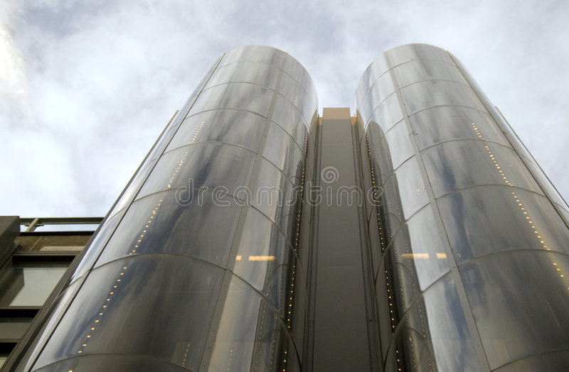 Modern glassy building on sky stock images