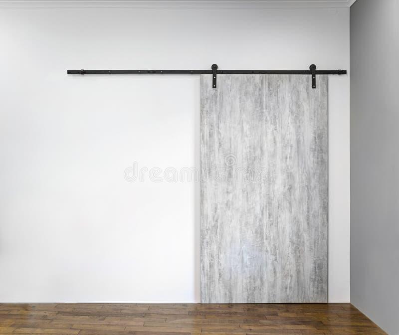 Modern glidande grå dörr på den vita väggen royaltyfria foton