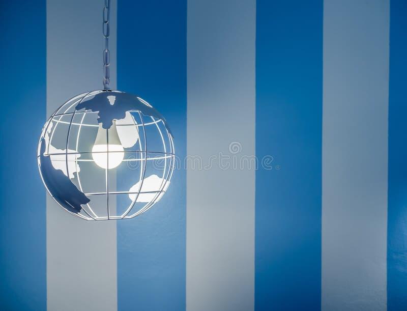 Modern global lampa för tak för jordvärldsform på väggbakgrund för vitt och blått band arkivbild