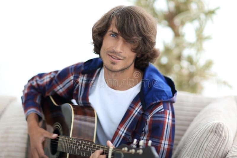 Modern grabb som spelar gitarrsammanträde på soffan begrepp av en livsstil arkivfoto