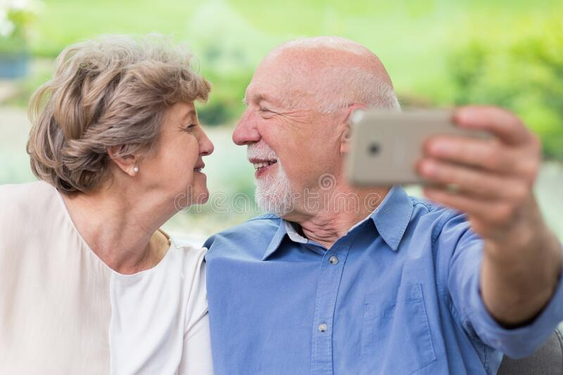 Grandpa and grandma looking for each other and taking selfie for social media account stock photo