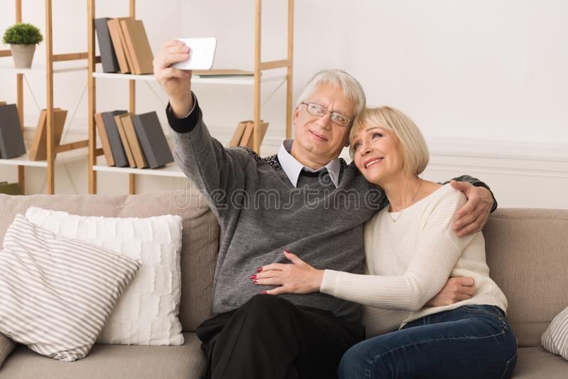 Modern Grandparents. Elderly Couple Making Selfie On Phone. At Home royalty free stock image