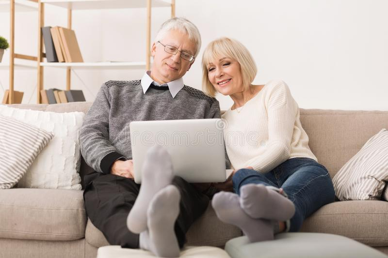 Modern Grandparents. Senior Couple Websurfing On Laptop royalty free stock photo