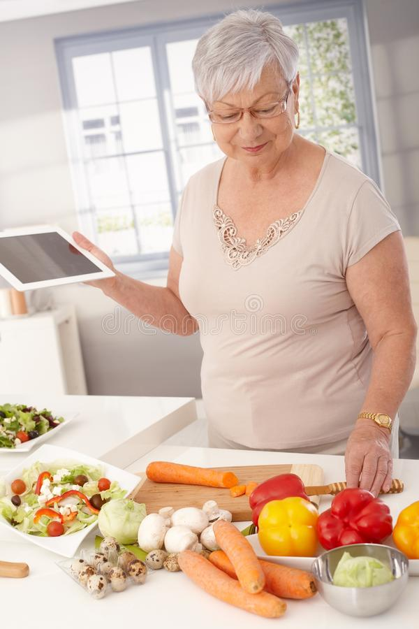 Modern granny cooking. Contemporary grandmother cooking healthy food, using tablet computer to prepare meal stock photography