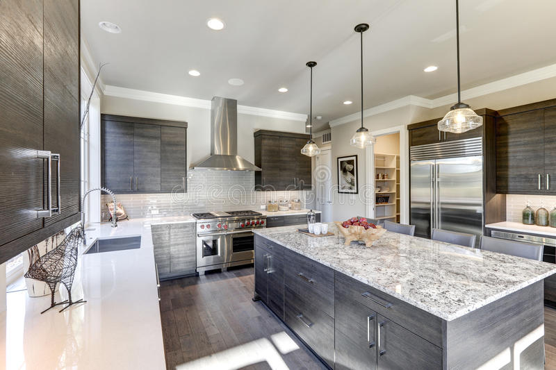 Modern gray kitchen features dark gray flat front cabinets. Paired with white quartz countertops and a glossy gray linear tile backsplash. Bar style kitchen royalty free stock images