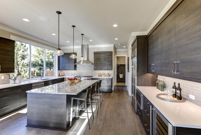 Modern gray kitchen features dark gray flat front cabinets. Paired with white quartz countertops and a glossy gray linear tile backsplash. Bar style kitchen stock images
