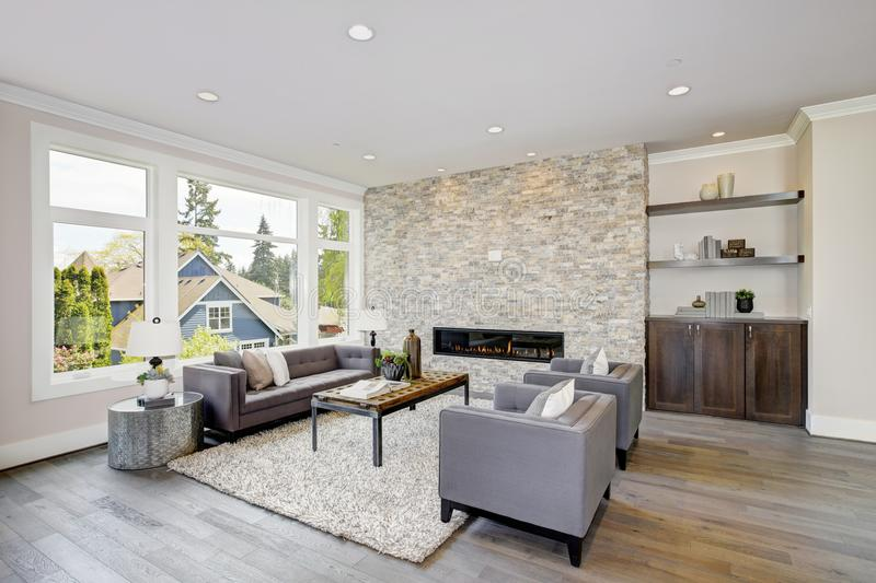 Modern great room with a floor to ceiling stone fireplace. Modern great room features a floor to ceiling stone fireplace, gray tufted sofa paired with two gray royalty free stock images