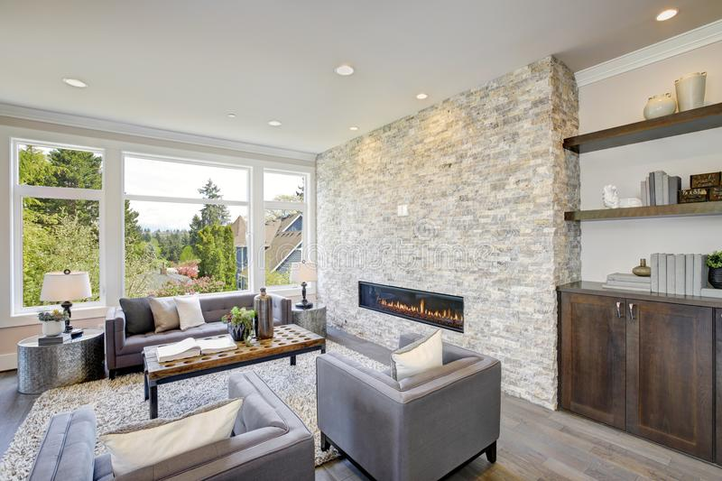 Modern great room with a floor to ceiling stone fireplace. Modern great room features a floor to ceiling stone fireplace, gray tufted sofa paired with two gray royalty free stock photos