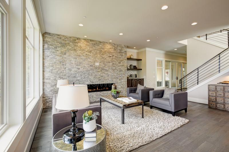 Modern great room with a floor to ceiling stone fireplace. Modern great room features a floor to ceiling stone fireplace, gray tufted sofa paired with two gray royalty free stock photography