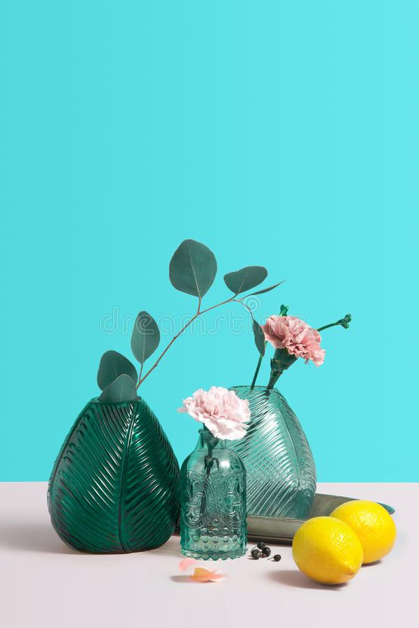 Modern green glass Vase with beautiful pink flowers. Creative Composition with flowers, lemon and vase on blue background. stock photography