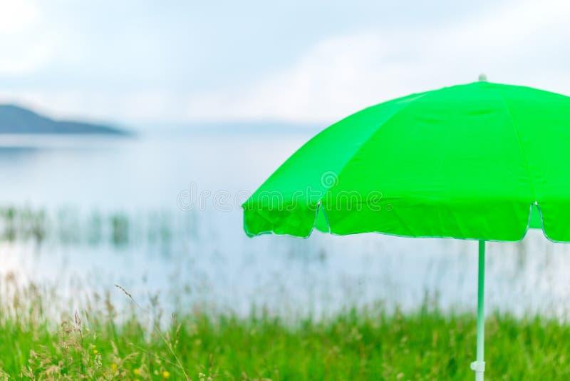 Modern green neon umbrella for sun on beach against sea.  stock images