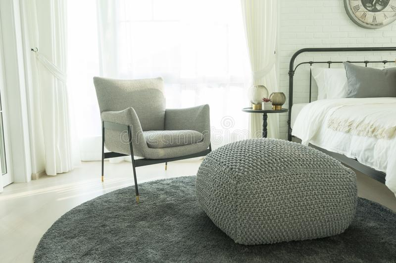Modern grey armchair next to bed with grey pillows in bedroom interior royalty free stock photo
