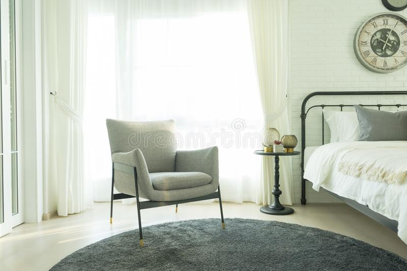 Modern grey armchair next to bed with grey pillows in bedroom interior royalty free stock photos