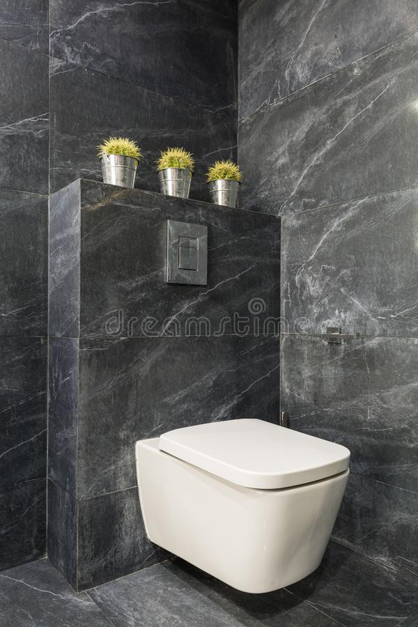 Modern grey bathroom with white toilet. Modern bathroom with white toilet seat and grey stone tiles stock photos