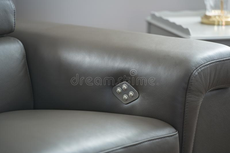 Modern grey leather sofa, with push button detail for recliner royalty free stock image
