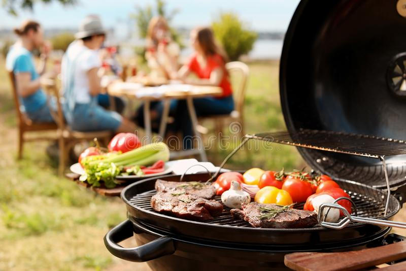 Modern grill with meat and vegetables outdoors royalty free stock images