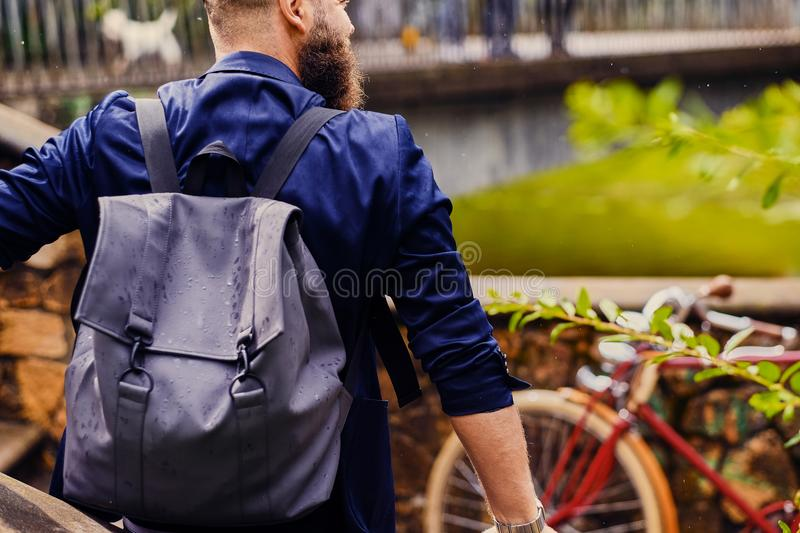 Modern guy with backpack. Back view. stock images
