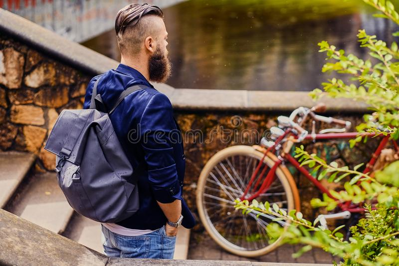 Modern guy with backpack. Back view. stock image